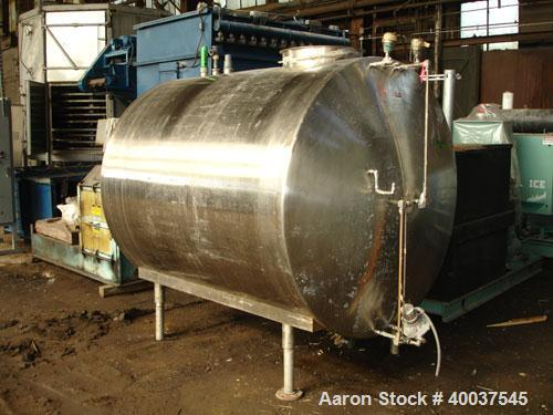 "Used- Tank, 1200 gallon, stainless steel, horizontal. Approximately 66"" diameter x 72"" straight side, dished ends. Top manwa..."